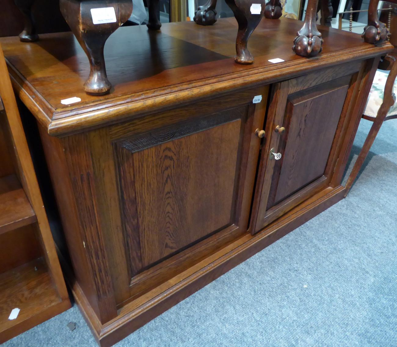 Tennants Auctioneers: An oak low two door cupboard
