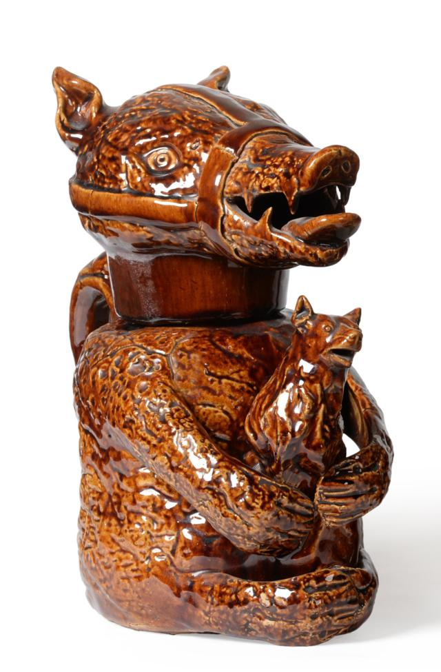 Tennants Auctioneers: A Treacle Glazed Pottery Bear Jug and Cover